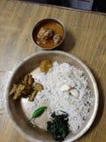 Una placa o un thali nepali t?pica en el ko de los chures thal Aqu? incluye un cuenco de carne, de veg, de un chile y de dos clav foto de archivo