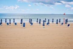 Una playa con los paraguas y las camas del sol en costa Imagen de archivo