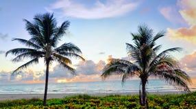 Una playa del sur de la Florida en la puesta del sol pone en evidencia la serenidad tranquila hacia fuera la arena y la resaca Foto de archivo