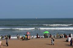 Una playa india con mucha gente que goza en la orilla de mar fotografía de archivo