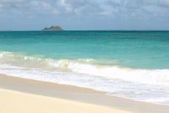 Una playa remota en Oahu, Hawaii con una opinión de la isla imagenes de archivo
