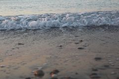 Una playa reservada y abandonada, ondas calientes apacibles que se arrastran lentamente hacia fuera sobre la orilla imagenes de archivo