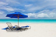 Una playa tropical con un poco de asientos y paraguas en la izquierda Imagenes de archivo