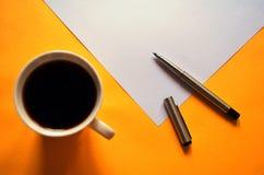 Una pluma abierta y una taza de café, durante una rotura del trabajo Imagenes de archivo