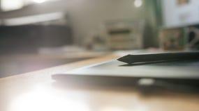 Una pluma de la tableta y de la aguja en una opinión de ángulo bajo a través del fotografía de archivo