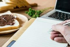 Una pluma de tenencia del hombre encima del cuaderno La tabla de funcionamiento incluye el ordenador portátil, el cuaderno y el d Imagenes de archivo