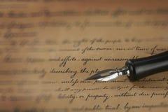 Una pluma del vintage en un papel manuscrito Foto de archivo