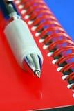 Una pluma en la tapa de un cuaderno rojo Imagenes de archivo