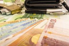 Una pluma más ligera del reloj del monedero en el fondo de las notas euro del dinero 100 Fotografía de archivo