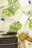 Una pluma más ligera del reloj del monedero en el fondo de las notas euro del dinero 100 Imágenes de archivo libres de regalías