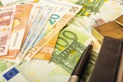 Una pluma más ligera del reloj del monedero en el fondo de las notas euro del dinero 100 Fotos de archivo