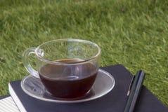 Una pluma, un cuaderno, y una taza de té en el césped fotos de archivo