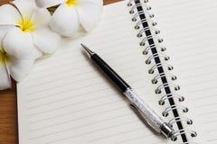 Una pluma y un cuaderno con la flor Foto de archivo libre de regalías
