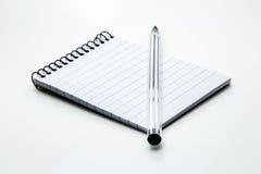 Una pluma y una libreta con un fondo blanco llano fotografía de archivo libre de regalías