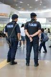 Una policía armada patrulla guardado en el pasillo del terminal de aeropuerto fotos de archivo