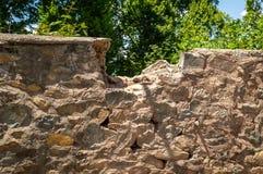 Una porción del top de una pared de piedra está quebrada foto de archivo