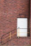 Una porta ad una funzione del muro di mattoni con le scale e una barra della maniglia immagine stock libera da diritti