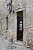 Una porta di legno antica, una lanterna del ferro e una scultura Pietà sopra la porta immagini stock