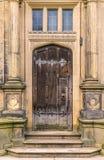 Una porta di legno marrone antica con le cerniere insolite immagini stock libere da diritti