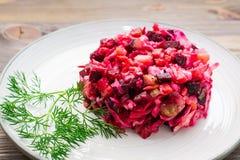 Una porzione di vinaigrette - un'insalata delle verdure bollite, dei crauti e dei cetrioli marinati su un piatto su una tavola di immagine stock libera da diritti