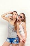 Una posa di due amici Stile di vita moderno Due migliori amici sexy alla moda delle ragazze dei pantaloni a vita bassa pronti per Immagine Stock Libera da Diritti