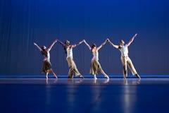 Una posa di quattro ballerini contro fondo blu scuro in scena Immagine Stock