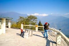 Una presa dell'uomo fotografie della montagna di Kanchenjunga dalla piazzola di eliporto di Pelling immagine stock libera da diritti