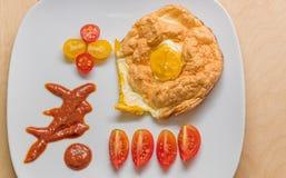 Una prima colazione deliziosa delle uova fritte e dei pomodori Fotografia Stock