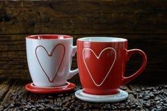 Una progettazione romantica di due tazze di caffè con i chicchi del modello e di caffè di forma del cuore Fotografie Stock Libere da Diritti