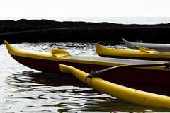 Una prora di tre canoe hawaiane che si siedono in acqua fotografia stock
