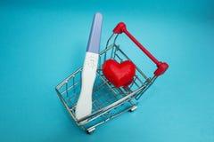 Una prueba de embarazo positiva y un corazón rojo en un carro de la compra foto de archivo libre de regalías
