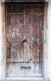 Una puerta antigua de madera de roble con la manija adornada del metal Fotos de archivo