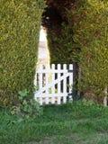 Una puerta blanca en un seto en Sunny Day imagen de archivo
