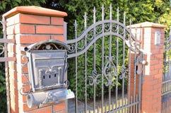 Una puerta de la cerca roja del ladrillo de escoria y del hierro labrado imágenes de archivo libres de regalías