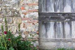 Una puerta de madera al lado de una pared de piedra Foto de archivo libre de regalías