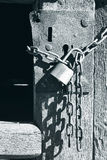 Una puerta de madera vieja se cerró con las cadenas y el candado Foto de archivo