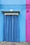 Una puerta en una pared azul de una casa colorida de la isla de Burano, VE Imágenes de archivo libres de regalías