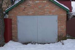 Una puerta gris del hierro cerrado en una pared de ladrillo marrón de un garaje afuera en la nieve blanca fotos de archivo