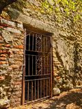Una puerta labrada antigua del irn en una pared romana de decaimiento foto de archivo libre de regalías