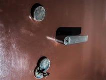 Una puerta segura marrón con dos llaves y una manija imagenes de archivo