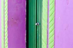 Una puerta verde de una casa violeta con las decoraciones verdes foto de archivo