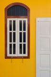 Una puerta y una ventana del vintage en la pared amarilla Imagen de archivo libre de regalías