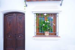 Una puerta y una ventana adornadas con las flores fotos de archivo