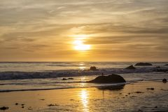 Una puesta del sol amarilla en la playa Fotos de archivo