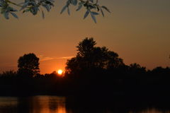 Una puesta del sol beautifal y un lago Foto de archivo