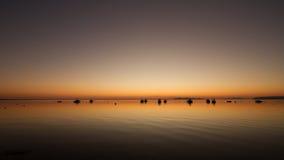 Una puesta del sol caliente en un agua tranquila, con las islas en el fondo Fotografía de archivo