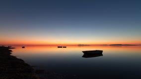 Una puesta del sol caliente en un agua tranquila, con las islas en el fondo Foto de archivo
