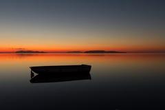 Una puesta del sol caliente en un agua tranquila, con las islas en el fondo Fotografía de archivo libre de regalías