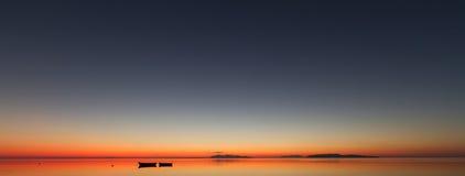Una puesta del sol caliente en un agua tranquila, con las islas en el fondo Imágenes de archivo libres de regalías