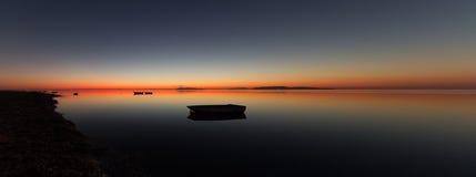 Una puesta del sol caliente en un agua tranquila, con las islas en el fondo Foto de archivo libre de regalías